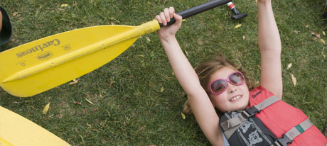 PHOTO: Young girl lying on the grass, lifting her paddle in the air.