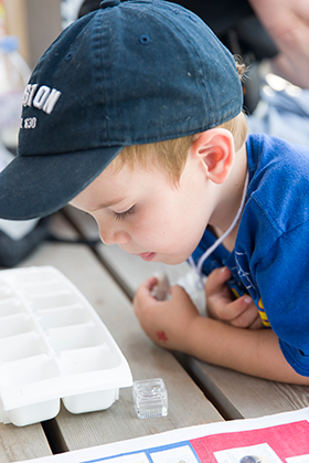 PHOTO: a boy examines river water samples in an ice tray