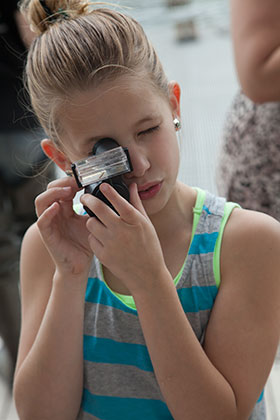 PHOTO: Girl examines pond life with a microviewer.