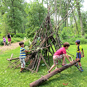 Boys making stick shelter while other children explore a path in the woods.